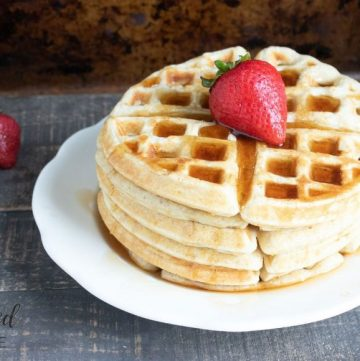stack of buttermilk waffles with a strawberry on top