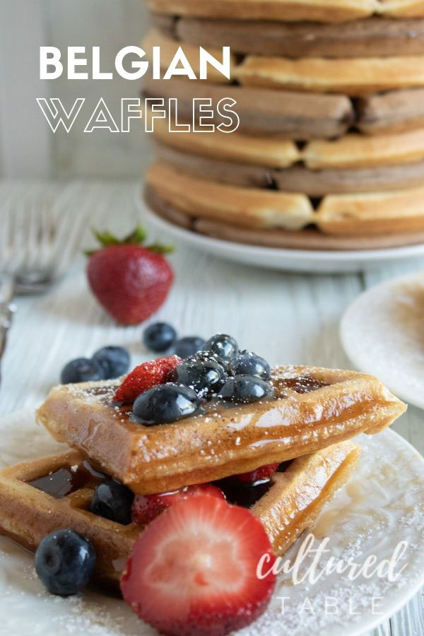 belgian waffle recipe on a white plate, topped with fresh blueberries and strawberries