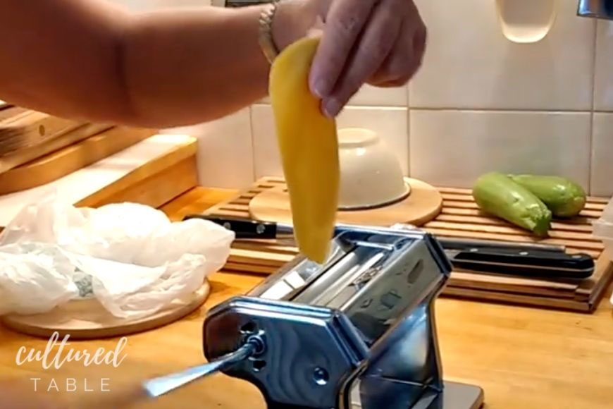 hand putting homemade dough into a pasta maker