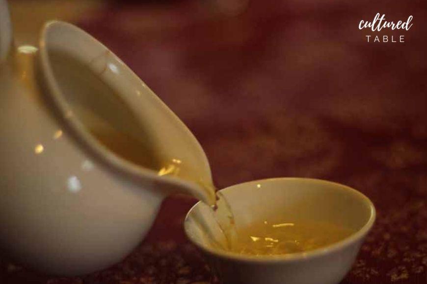 porcelain pot pouring light yellow liquid