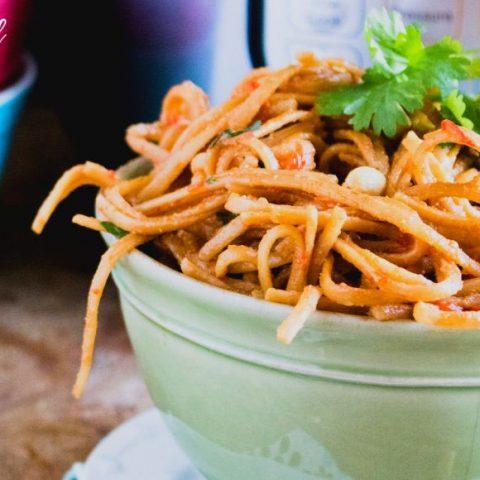 thai peanut noodles in a green bowl