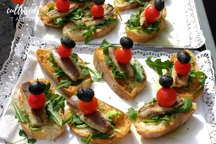 sardines on crusty bread with a cherry tomato