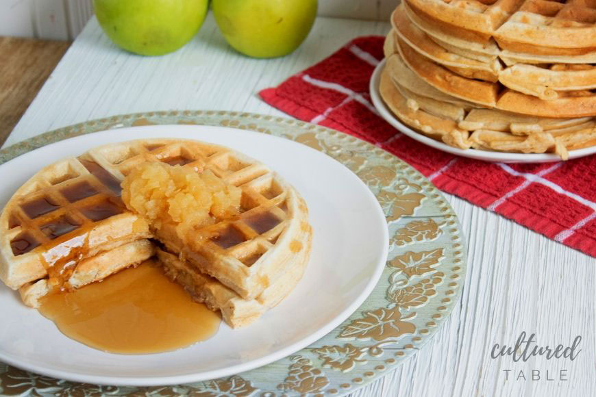 waffles with a scoop of applesauce on a white plate