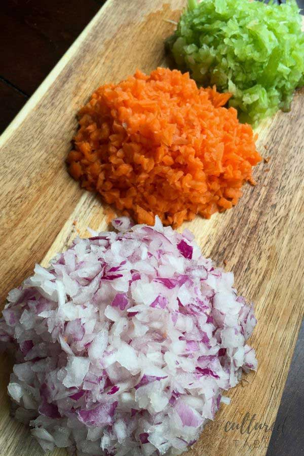 piles of diced celery, carrot, red onion on a wooden tray