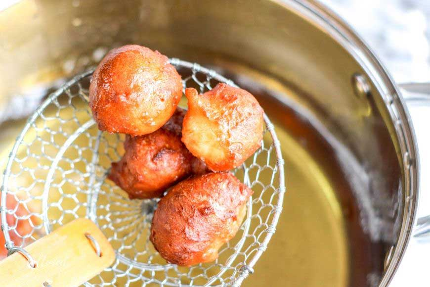 fried greek donuts on a wire skimmer