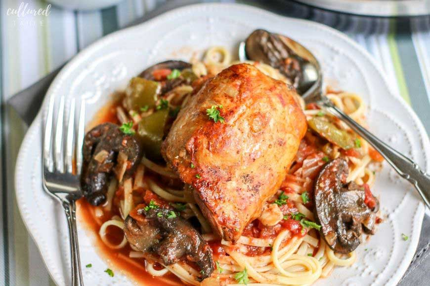 slow cooker chicken cacciatore on a pretty white plate with noodles
