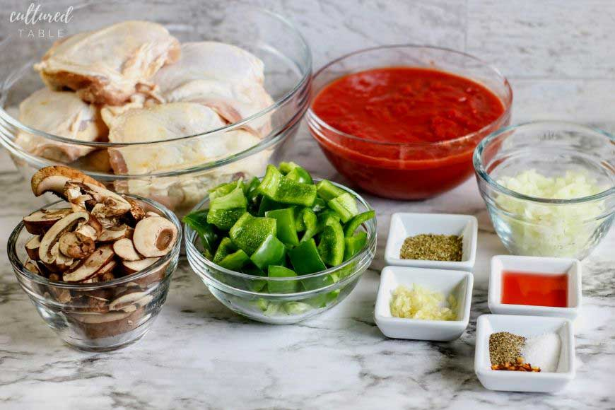ingredients for chicken cacciatore on a marble counter