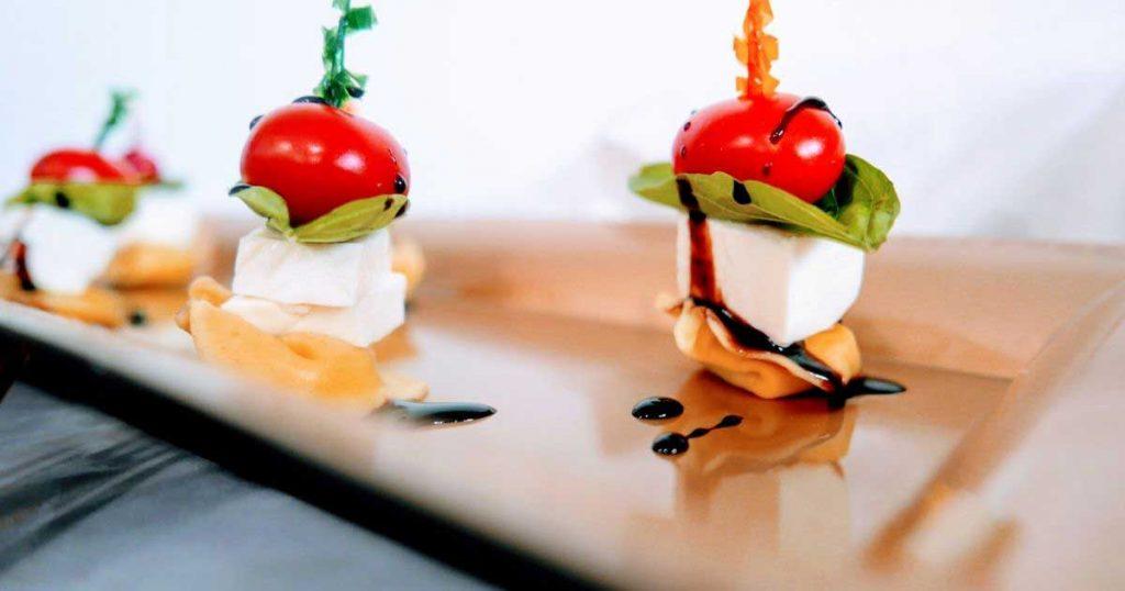 caprese appetizers: skewers with tortellini, mozzarella, basil, tomato