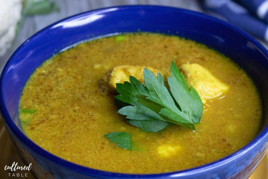 close up of chicken curry soup in a cobalt blue bowl