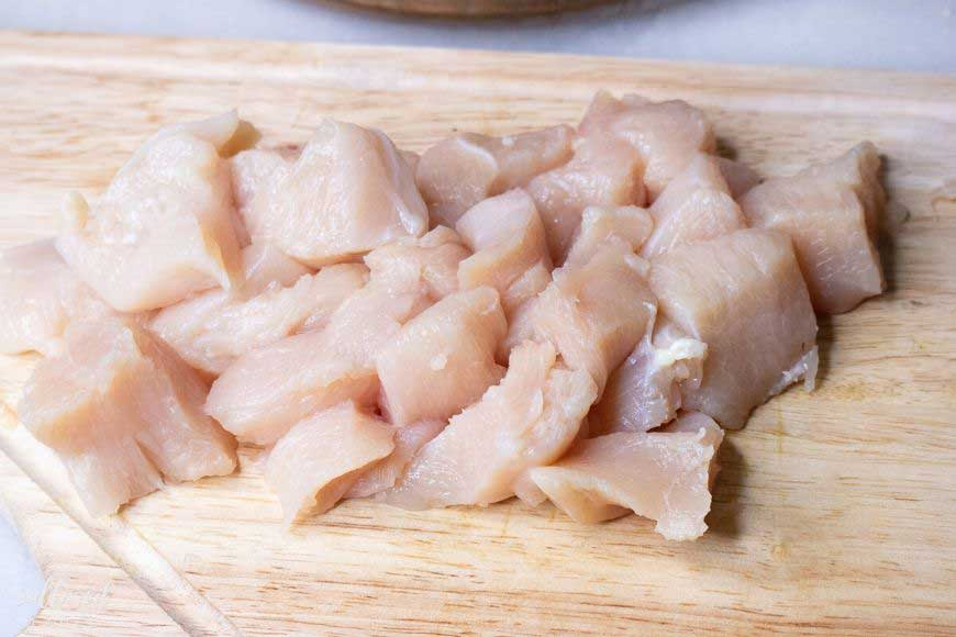 cut up chicken breasts on a cutting board