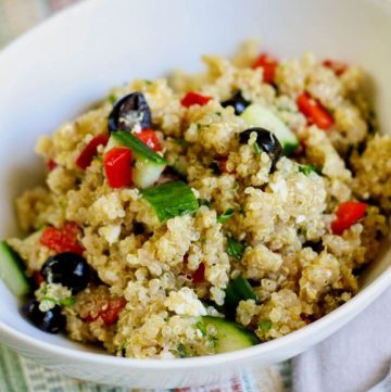 grainy salad in a white bowl with cucumber and red pepper