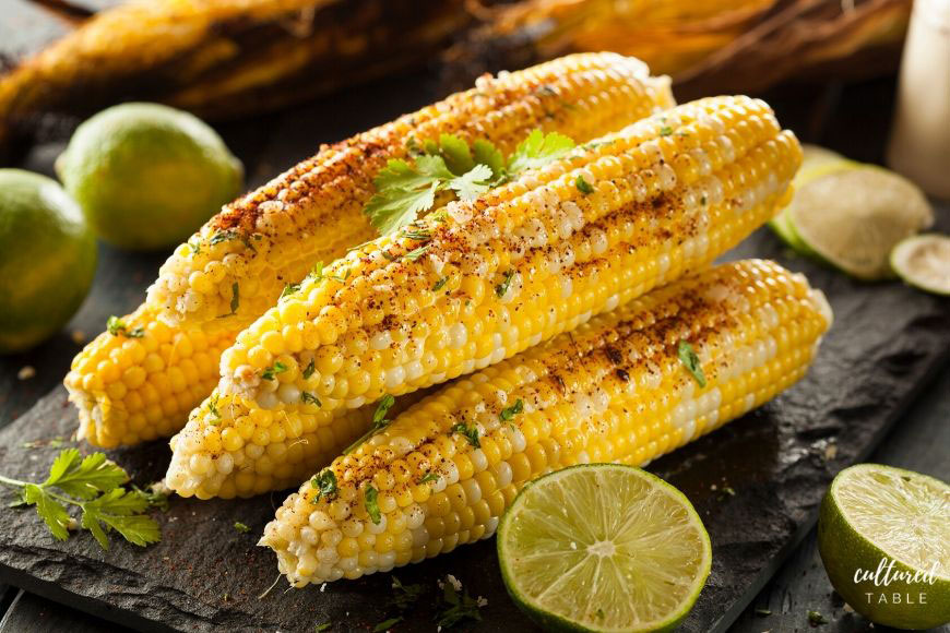 elote or corn on the cob in a stack with cut limes