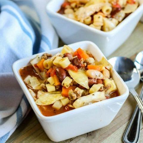 pasta e fagioli in a square bowl with a spoon