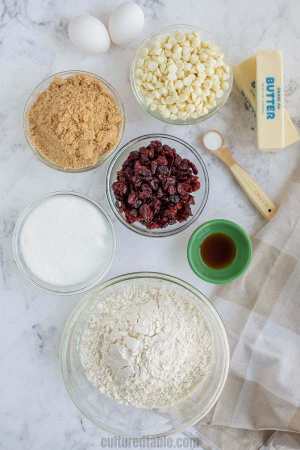 ingredients for white chocolate chip cookies in glass bowls from above