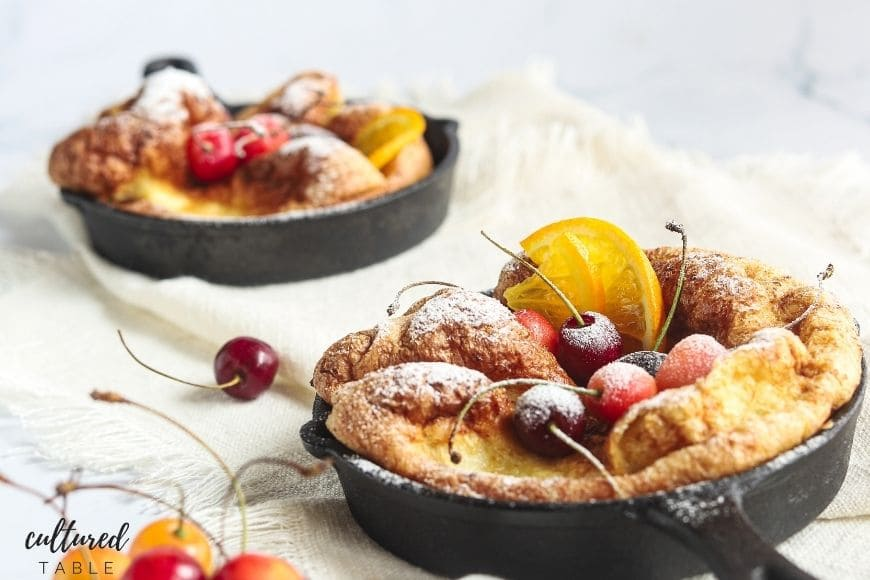 dutch baby pancakes in a small cast iron skillet with fruits on top