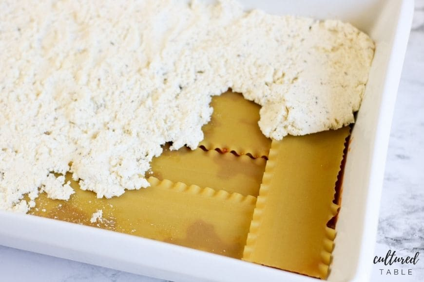 uncooked lasagna layers with ricotta cheese and uncooked pasta