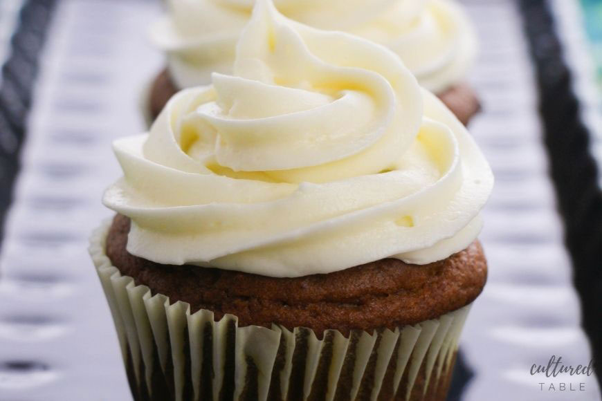 close up of cupcake with white swirled frosting