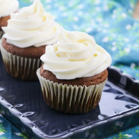 FROSTED pumpkin cupcakes on a blue rectangular platter