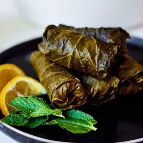 stuffed grape leaves on a black plate with orange slices and mint