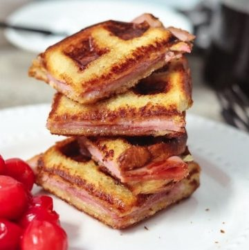 monte cristo recipe sandwich cut and stacked with cherries on the side
