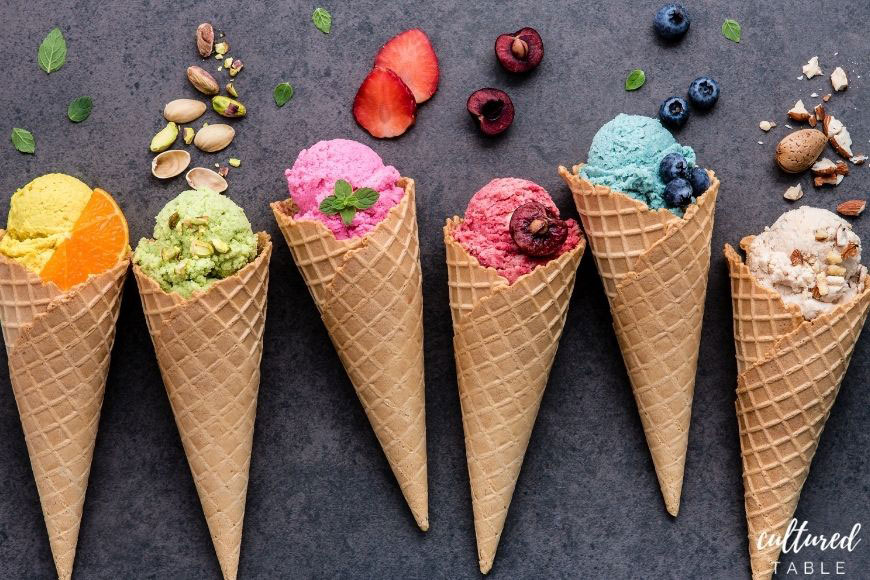 various Italian gelato flavors in waffle cones on a grey background