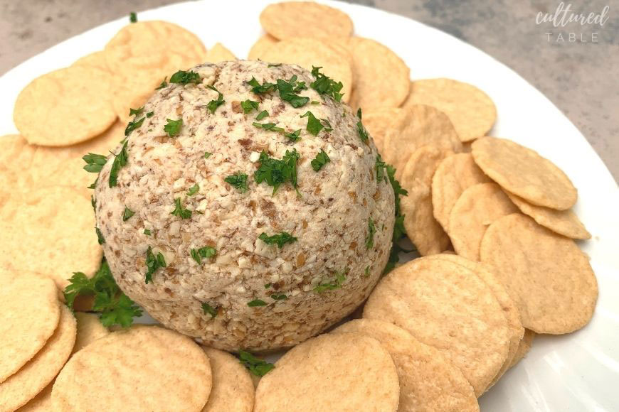 classic cheese ball on a white plate with crackers
