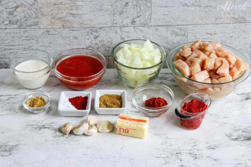 ingredients for instant pot butter chicken on a marble background