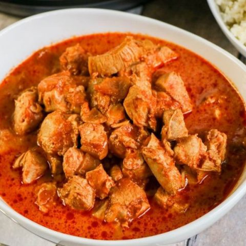 indian butter chicken (red stew) in a white bowl