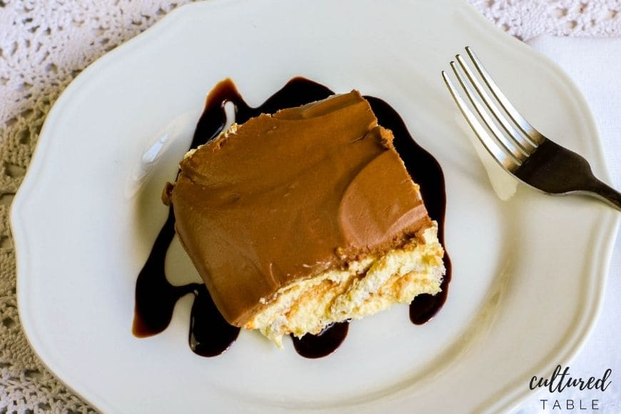no bake eclair cake on a white plate with chocolate drizzle