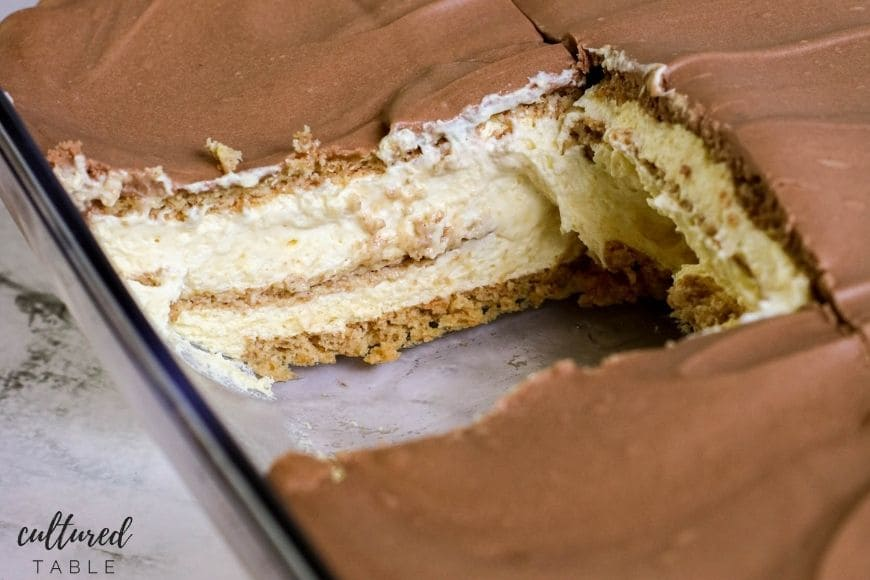 no bake chocolate eclair cake in a glass pan with piece removed