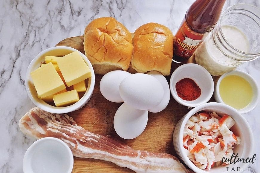 blocks of butter, eggs, buns, crab, and bacon on cutting board