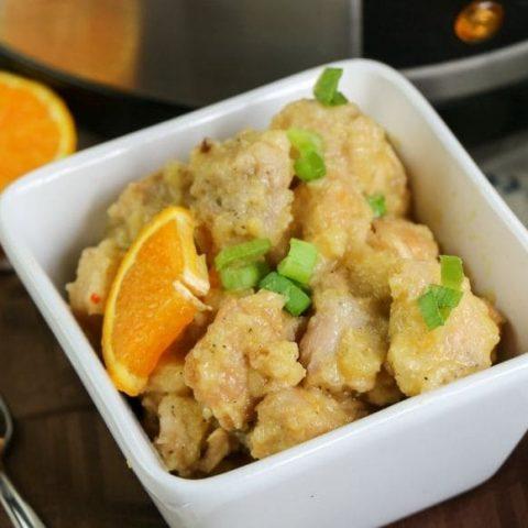 orange chicken in a white square bowl