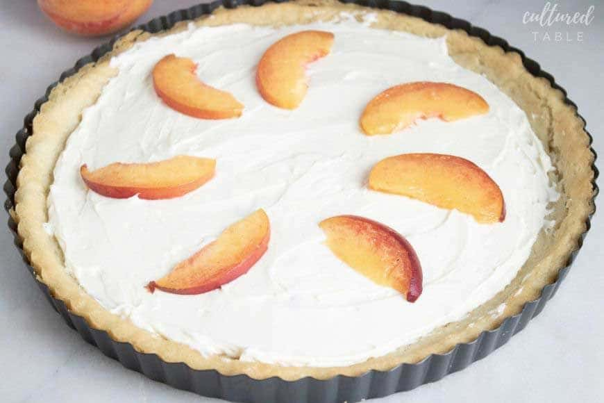 frosting on a peach tart with peach slices