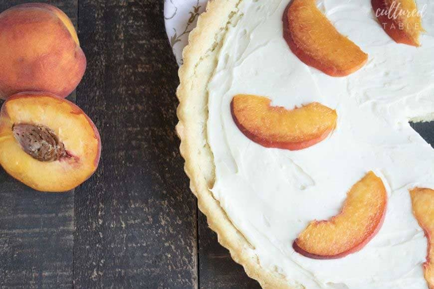 cookie dough peach tart on a dark wood background