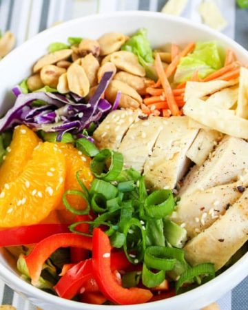 Asian chicken salad in a white bowl showing ingredients grouped together (red pepper, mandarin, chicken, green onions, peanuts)