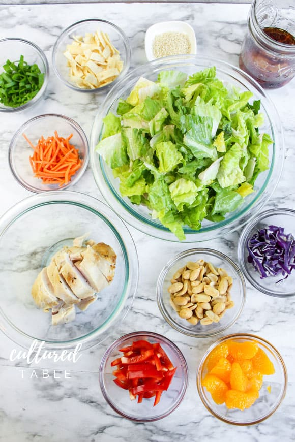 salad ingredients in clear glass bowls on a marble background