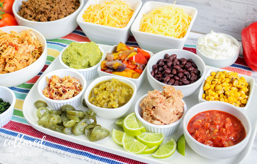 variety of white dishes filled with ingredients for a quesadilla bar - cheese, meat, beans, sour cream, guac...