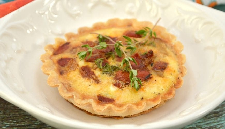 savory tartlet with red peppers on a white embossed plate