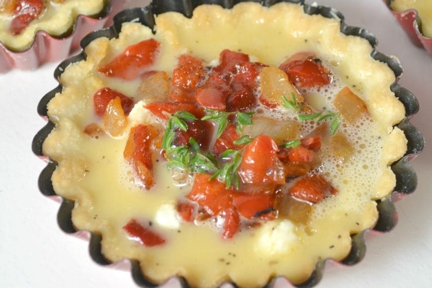 mini tart pan filled with egg and veggies before cooking
