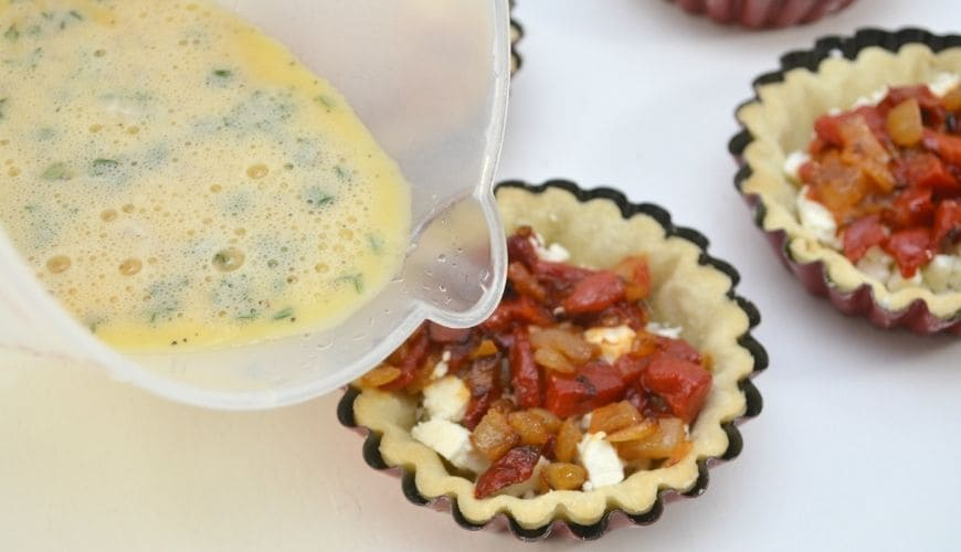 measuring cup pouring egg into filled tartlets