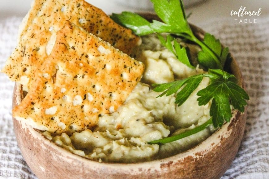 light green baba ganoush in a wooden bowl with crackers