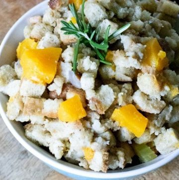 bowl of bread dressing with butternut squash and rosemary garnish